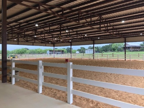 Indoor arena with white fence by Covered Arena (TM) and Dressage Arenas